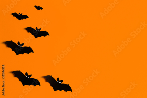 Photo orange background with a flock of black paper bats for Halloween, black paper ba
