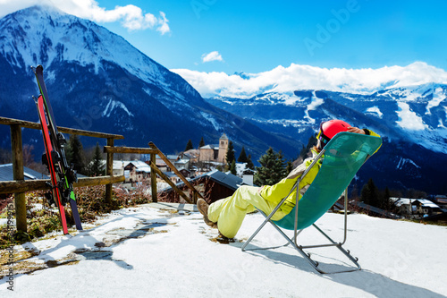 Photo Young woman rest in the deck chair near pair of ski observing mountains and Alpi