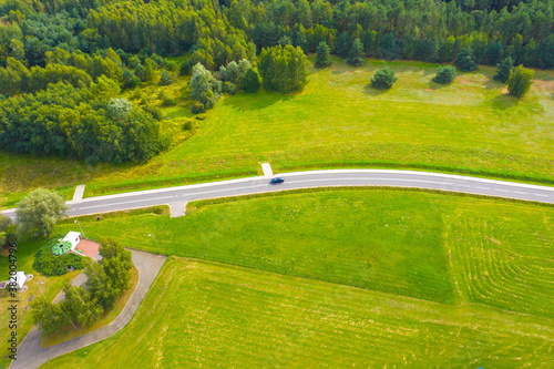 Fototapeta Aerial view of car driving on road along the green forest and potato with yellow rapeseed fields in rural landscape in summer obraz