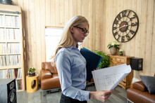 Woman Holding Plans In Rustic ...