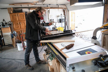 Male Carpenter Using Table Saw...