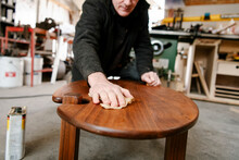 Male Carpenter Staining Wood T...