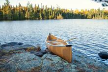 Yellow Canoe On Rocky Shore Of Northern Minnesota Lake At Sunrise During Autumn