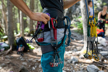Close Up Young Man Preparing Rock Climbing Harness In Woods