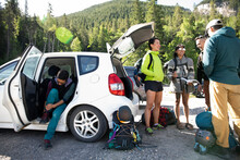 Young Friends Preparing For Rock Climbing At Car In Sunny Parking Lot