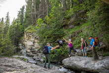 Female Hiker Throwing Backpack...