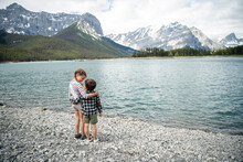 Affectionate Brother And Sister Hugging At Tranquil Mountain Lakeside