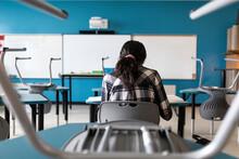 Student Sitting At School Desk...