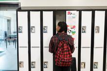 Student Standing By Open School Locker