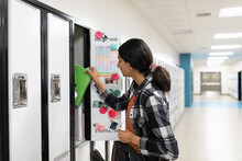 Student Using Locker In School Corridor