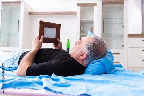 Old man drinking wine in the bedroom Fototapet