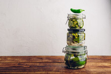 Three Glass Jars Of Freshly Canned Jalapeno Peppers With Herbs And Garlic On Wooden Table. Copy Space