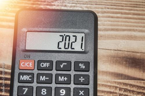 Fototapeta Black electronic calculator on dark wooden background, numbers show 2021 obraz
