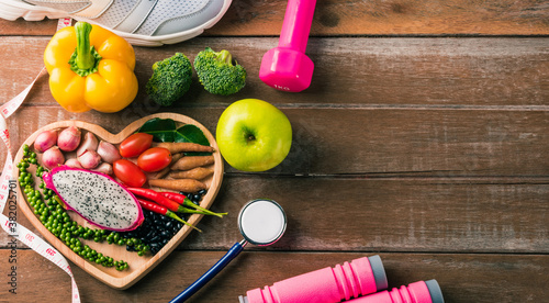 Fototapeta Top view of fresh organic fruit and vegetable in heart plate, shoes, sports equipment and doctor stethoscope, studio shot on wooden gym table, Healthy diet vegetarian food concept, World food day obraz