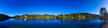 A Breathtaking Panoramic Aerial Shot Of The Still Deep Blue Water, Blue Sky And Lush Green Trees And Lake Front Homes At Lake Gregory In The San Bernardino National Forest In California