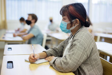 Diligent Asian Teen Girl In Protective Mask Studying In College With Classmates. New Life Reality In Coronavirus Pandemic