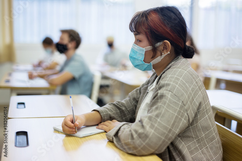 Diligent asian teen girl in protective mask studying in college with classmates Fototapet