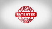 Patented Signed Stamping Text Wooden Stamp Animation. Red Ink On Clean White Paper Surface Background With Green Matte Background Included.