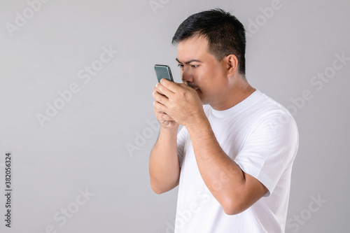 Foto Short or long sighted concept : Man trying to look closer on smarthphone in stud