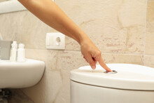 Woman Hand Presses The Toilet ...