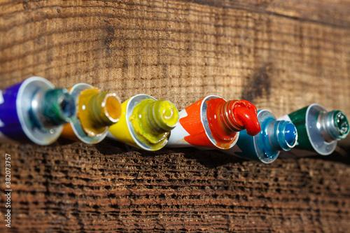 Olejne farby w tubce, na tle starego, chropowatego drewna.