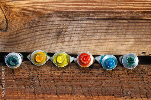 Olejne farby w tubce, na tle starej chropowatej deski.