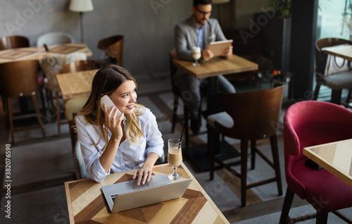 Fototapeta Portrait of a young beautiful businesswomen enjoying coffee during work on laptop computer, obraz