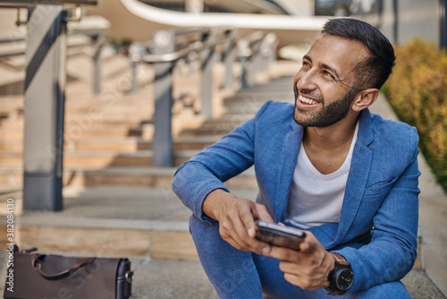 Smiling Indian arabic business man sitting on staircase using mobile a phone Canvas