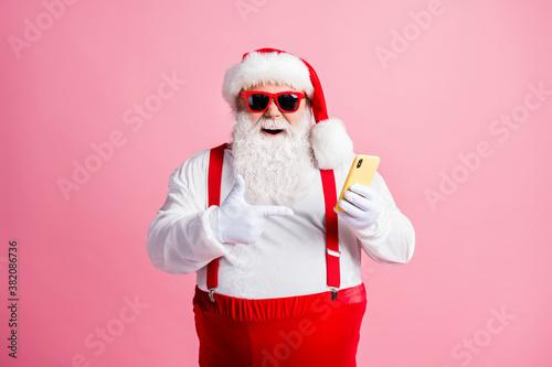Fotografiet Portrait of his he nice attractive cheerful bearded fat guy Santa using demonstr