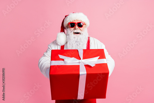 Obraz Portrait of his he nice attractive cheerful cheery Santa father holding in hands giving handling large giftbox congratulation congrats greetings North Pole isolated over pink pastel color background - fototapety do salonu