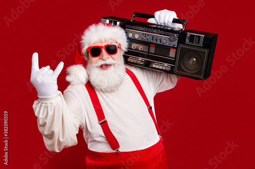 Fototapeta Close-up portrait of nice handsome cool cheery bearded Santa father hipster carrying boombox having fun show horn sign heavy metal celebratory isolated bright vivid shine vibrant red color background obraz