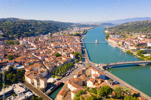 General view of Vienne city on banks of Rhone river surrounded by high hills in sunny summer day, Isere, France