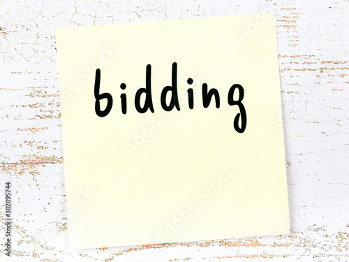Tablou Canvas Yellow sheet of paper with word bidding. Reminder concept