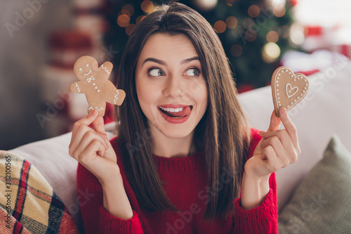Fotomural Portrait of addicted girl hold x-mas man heart shape ginger bread cookies tongue
