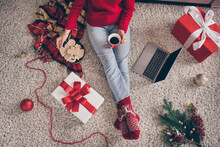 High Angle View Cropped Photo Of Young Woman Sit Carpet Netbook Hold Cup Cookies Wear Red Sweater Socks Jeans In X-mas Living Room Indoors