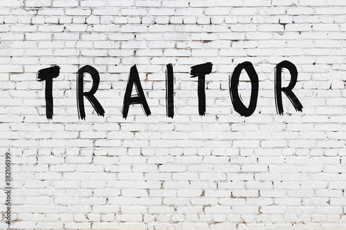 Inscription traitor painted on white brick wall Fototapeta