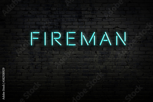 Cuadros en Lienzo Night view of neon sign on brick wall with inscription fireman
