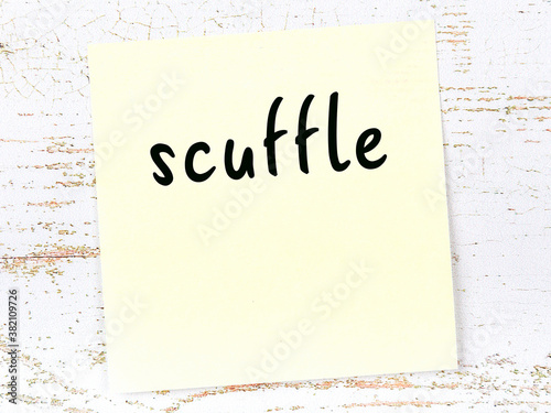 Fotografia Yellow sticky note on wooden wall with handwritten word scuffle