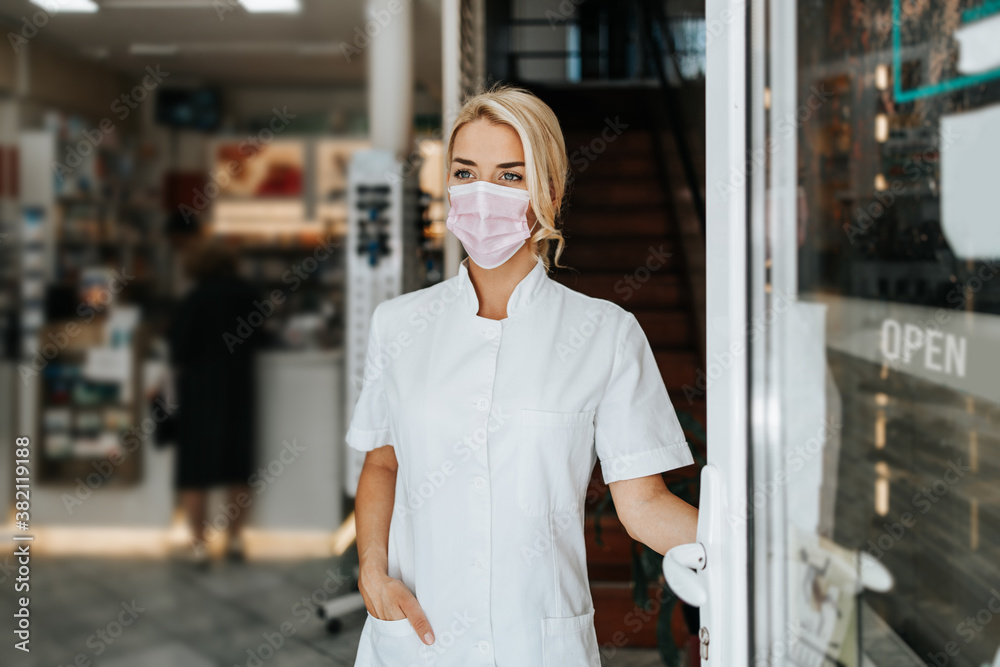 Fototapeta Young and attractive female pharmacist with face protective mask standing at open drugstore doors and looking outside. She is confident and serious. Covid-19 open for business concept.