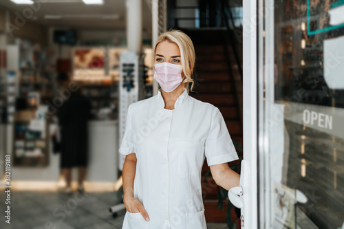 Obraz Young and attractive female pharmacist with face protective mask standing at open drugstore doors and looking outside. She is confident and serious. Covid-19 open for business concept. - fototapety do salonu
