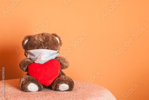 Fototapeta Love in times of COVID-19 quarantine Cute teddy bear with big, red heart