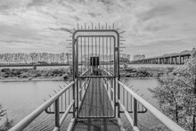 Metal Bridge With A Closed Door Prohibiting Passage, Bare Trees And Road Bridge A76 (Scharbergbrug) Over The Maas River In The Background, South-Limburg In The Netherlands. Black And White Image