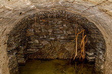 Underground Stone Canal With Tree Roots Running Through The Walls With Clean Water In The Clervaux Forest, Luxembourg