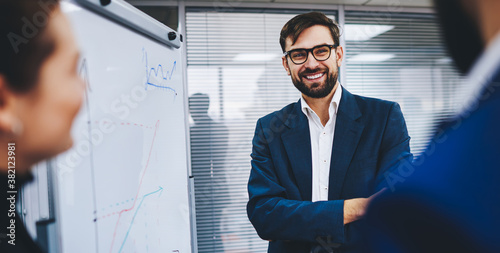 Cheerful male leader of company smiling near flip chart during presentation with colleagues, happy businessman in formal outfit and spectacles discussing economic graphics with cropped partners