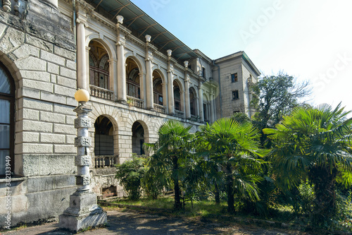 Tela Old grey stone building with columns and balconies and balusters in a Park with
