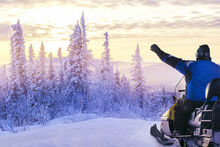 Man On Snowmobile At Sunset Wi...
