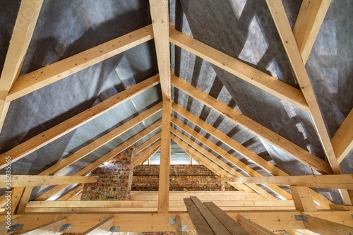 Attic of a building under construction with wooden beams of a roof structure and brick walls Poster Mural XXL