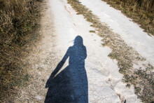 Silhouette Of A Girl On A Chalk Road.