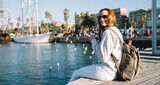 Portrait of cheerful hipster girl in stylish sunglasses resting near harbor during summer vacations holding cellphone for blogging and smiling at camera, happy woman with backpack enjoying leisure