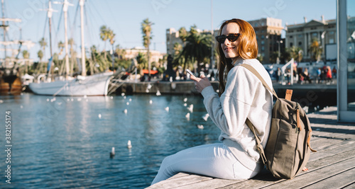 Fototapeta Portrait of cheerful hipster girl in stylish sunglasses resting near harbor during summer vacations holding cellphone for blogging and smiling at camera, happy woman with backpack enjoying leisure obraz